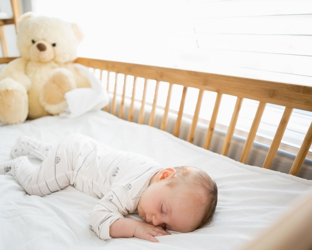 baby napping on stomach in crib