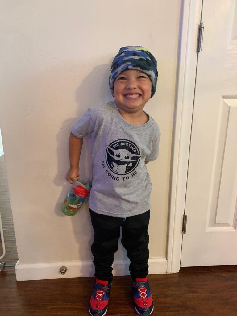 little boy wearing a big brother Star Wards shirt