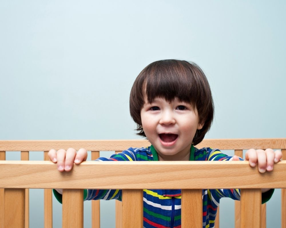 two year old standing up in crib