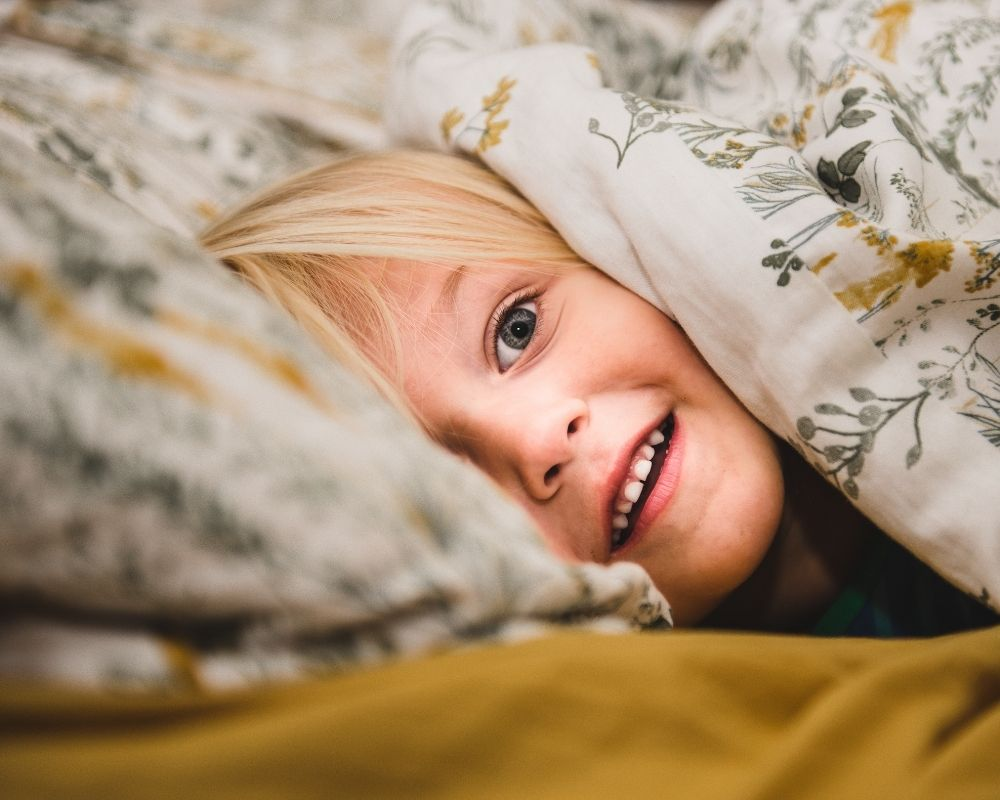 toddler peeking through comforter in bed