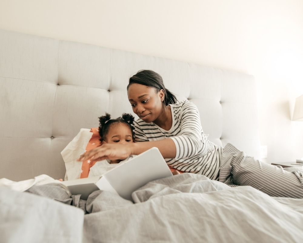 mom and girl reading together at bedtime