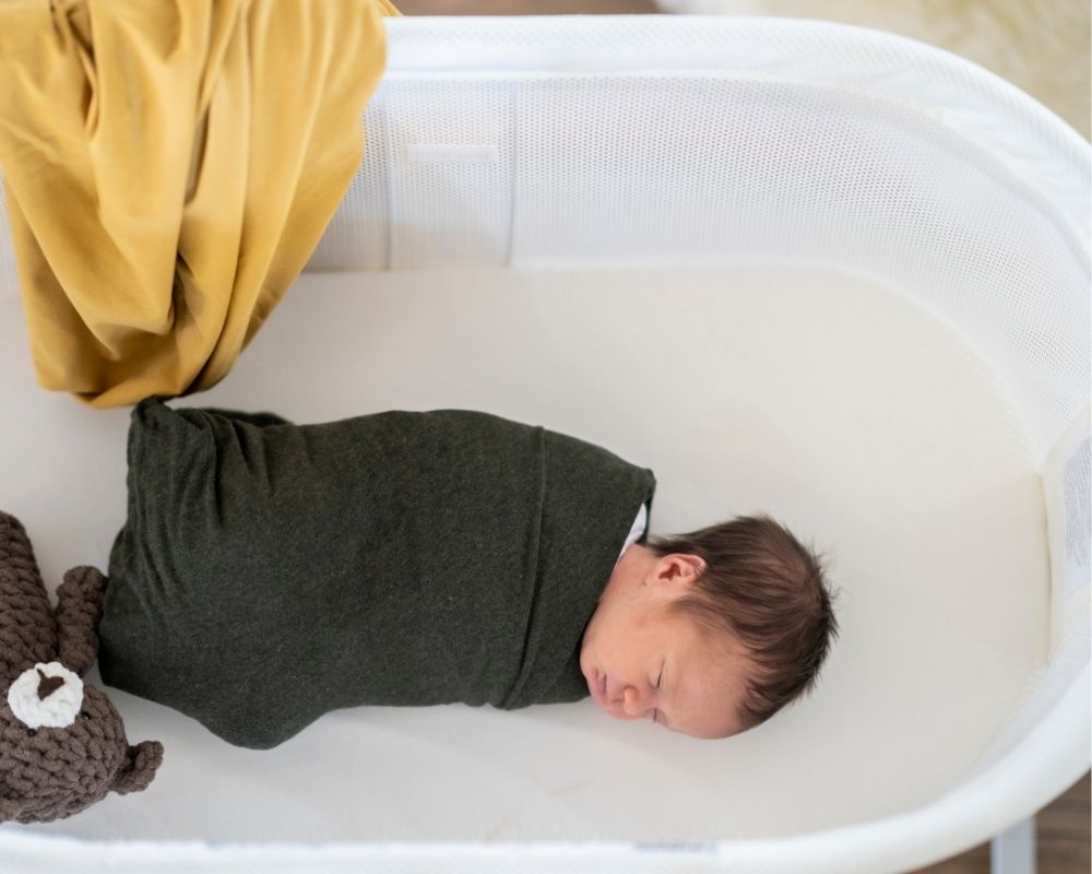 baby swaddled in bassinet