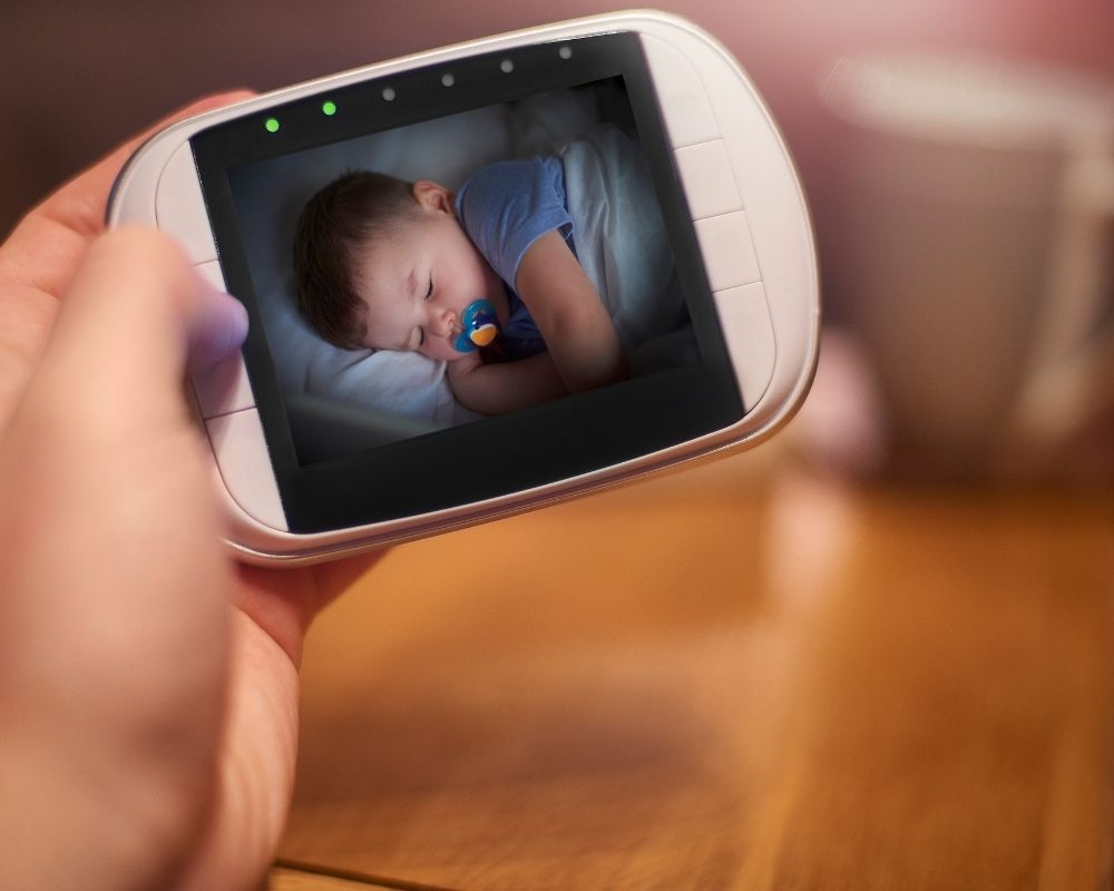 mom holding video monitor with baby sleeping