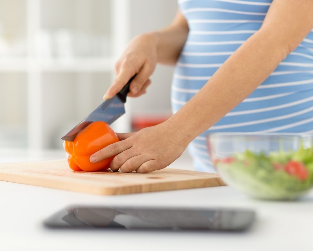 pregnant woman prepping food